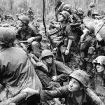 Vietnam War Tour - American infantrymen crowd into a mud-filled bomb crater and look up at tall jungle trees seeking out Viet Cong snipers firing at them