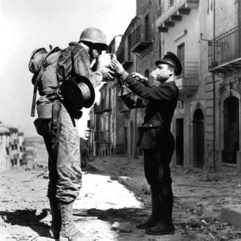 An Italian civilian policeman provides an American soldier a refreshing drink of water following Operation Husky - Italy Battlefield Tours