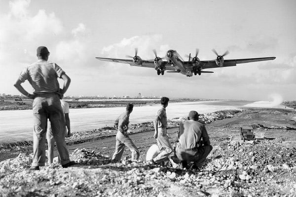 American soldiers watch a B-29 Superfortress heavy bomber take off from the now Allied controlled island of Saipan in the Pacific Dec 1944 - Guadalcanal 75th Anniversary Tour