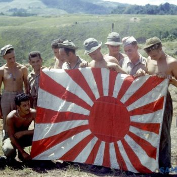 American troops holding Japanese flag at South Pacific island base following their convoy's arrival at Guadalcanal - Guadalcanal 75th Anniversary Tour
