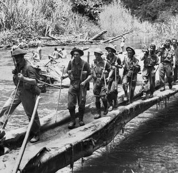 About 20 soldiers use a simple bridge that is little more than a pair of logs - Milne Bay 75th Anniversary Tour