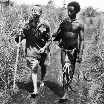 "A Papua New Guinean Native ""Fuzzy Wuzzy Angel"", guiding an injured Australian soldier home - Trek Kokoda Tour"