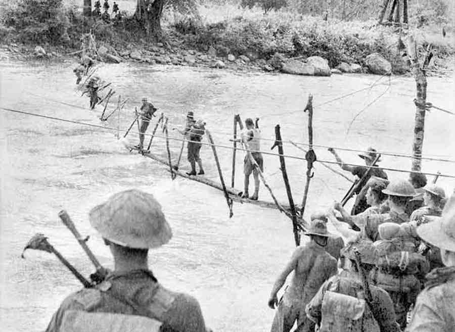 Advancing to the coast Australian soldiers crossing an improvised bridge over the Kumusi River at Wairopi - Trek Kokoda Tour