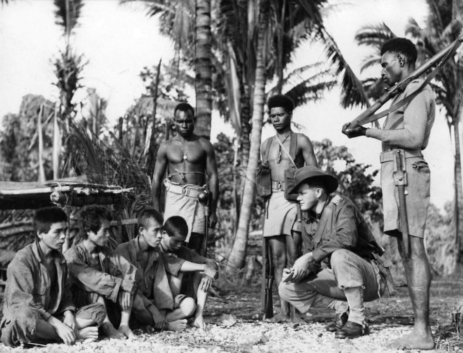 Japanese soldiers are interrogated by an Australian soldier, with local island natives standing guard - Trek Kokoda Tour