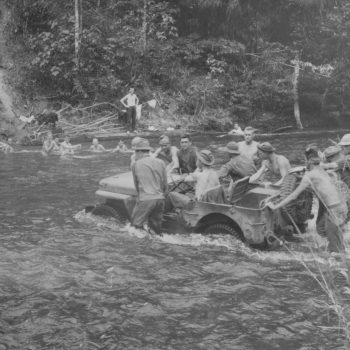 "An army scout car takes a jungle stream in New Guinea with ease - - more or less. While soldiers push, some of their buddies watch from the ""privacy"" of their bath - Beachheads Tour"