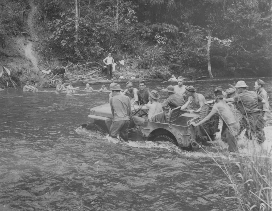 """An army scout car takes a jungle stream in New Guinea with ease - - more or less. While soldiers push, some of their buddies watch from the """"privacy"""" of their bath - Beachheads Tour"""