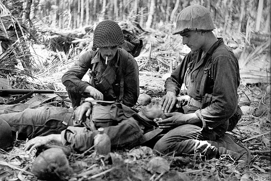 During the Australian-American advance on Buna two American soldiers dress the wounds of an Australian Beachheads Tour