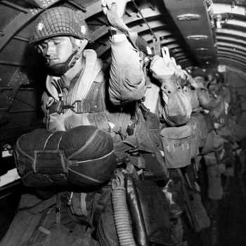 U.S. paratroopers fix their static lines before a jump before dawn over Normandy on D-Day - Normandy D-Day Tour